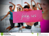 Fit-blonde-holding-card-saying-join-us-against-zumba-class-gym-39437785